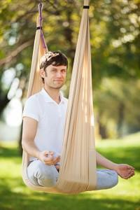 Man gör AntiGravity yoga utomhus