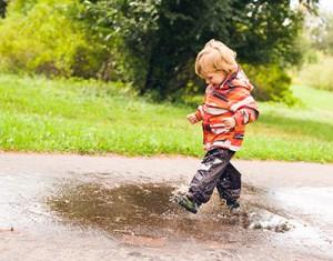 Barn springer i vattenpöl